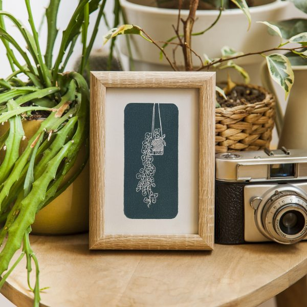 Hand carved lino block print of a hanging plant in a macrame holder on handmade paper in wooden frame surrounded by house plants and camera