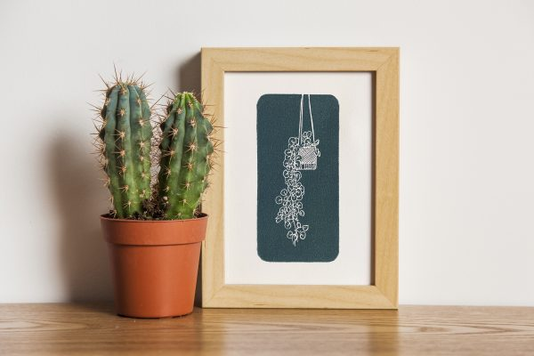 Hand carved lino block print of a hanging plant in a macrame holder on handmade paper in wooden frame next to mini potted cactus