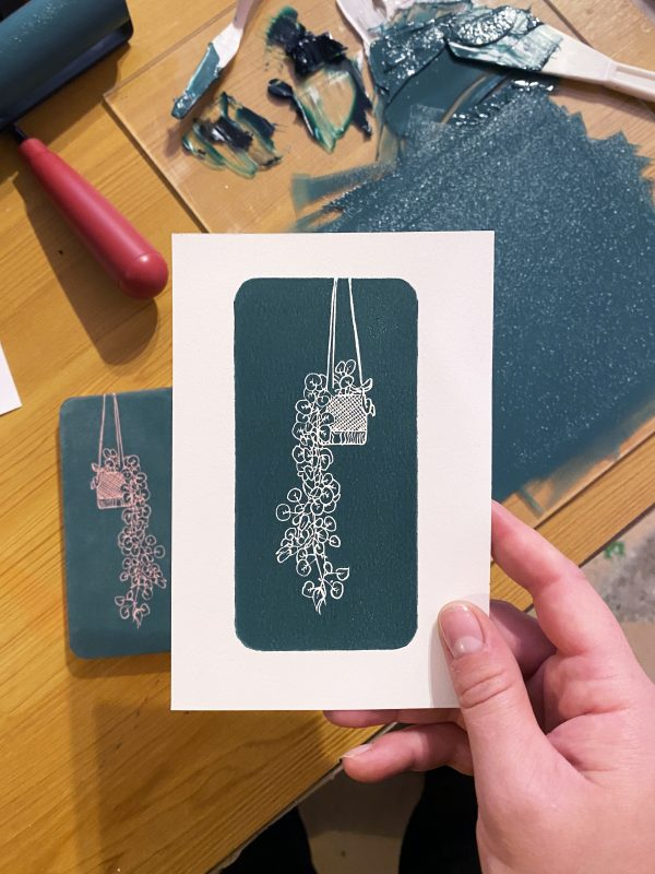 Hand carved lino block print of a hanging plant in a macrame holder on stonehenge paper - green blue ink - held by the creator in the studio - print materials can be seen in the background