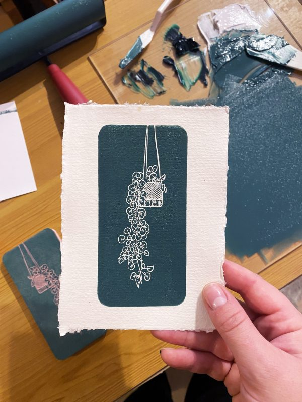 Hand carved lino block print of a hanging plant in a macrame holder on handmade paper held by the creator in the studio - print materials can be seen in the background